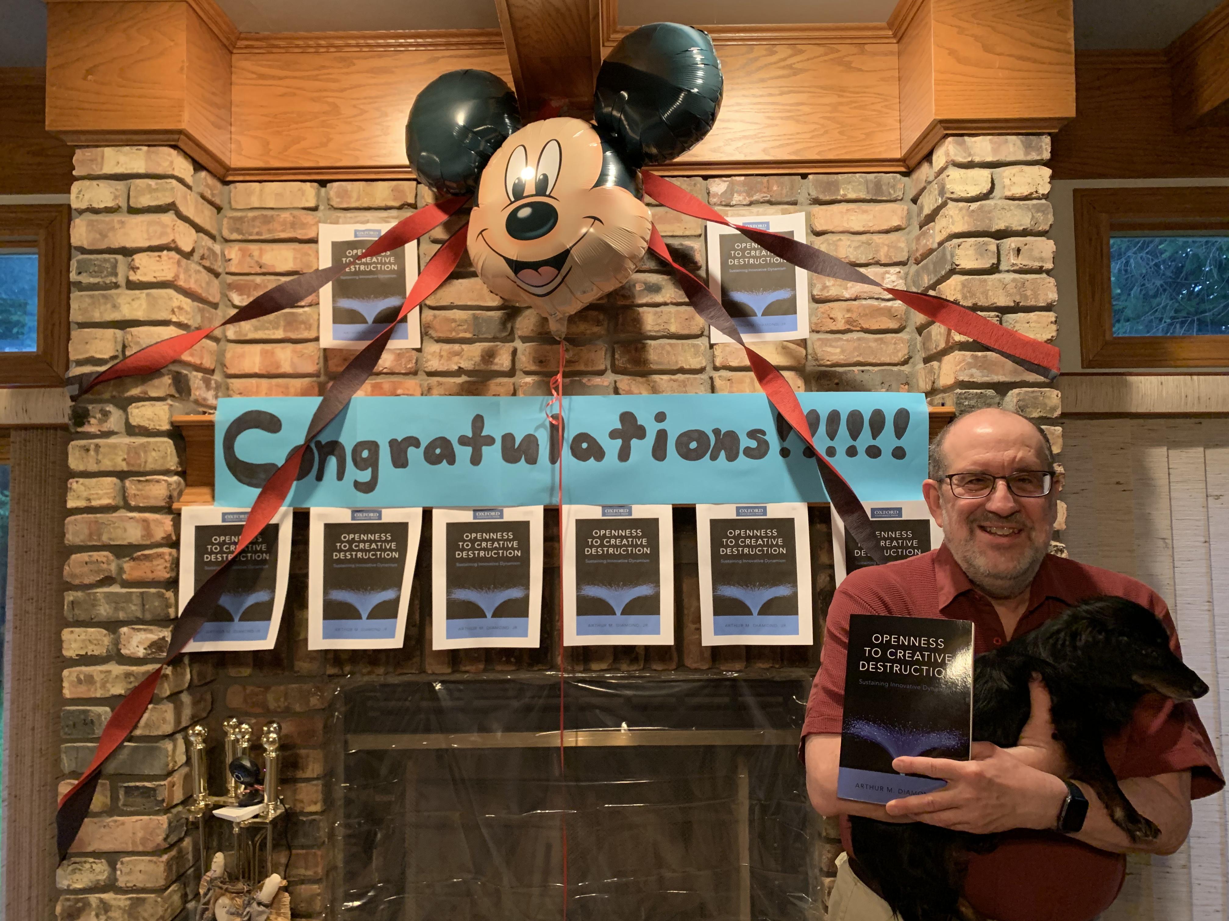 "Art Diamond next to sign saying ""Congratulations!""."